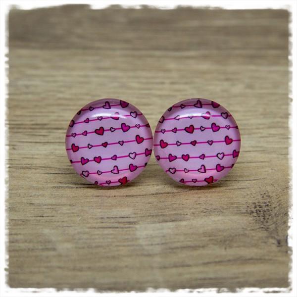 1 Paar Ohrstecker mit Herzen auf rosa Hintergrund