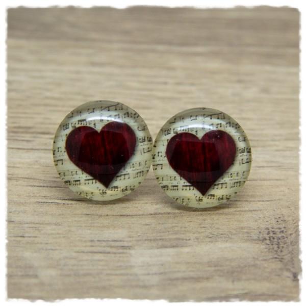 1 Paar Ohrstecker mit Herz auf beigem Hintergrund
