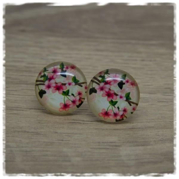 1 Paar Ohrstecker mit Ästen und pinken Blüten auf beigem Hintergrund