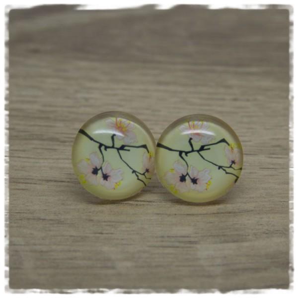 1 Paar Ohrstecker mit Ast und rosa Blüten auf gelbem Hintergrund