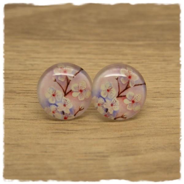 1 Paar Ohrstecker mit weißen Blüten auf rosa Hintergrund